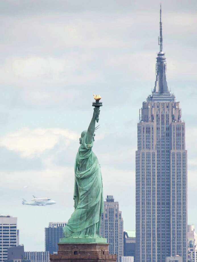 This photo provided by NASA shows Space shuttle Enterprise, riding on the back of the NASA 747 Shuttle Carrier Aircraft, flies near the Statue of Liberty, Friday, April 27, 2012,in New York. (AP Photo/NASA, Bill Ingalls) Photo: NASA/Bill Ingalls, Associated Press / (NASA/Bill Ingalls)
