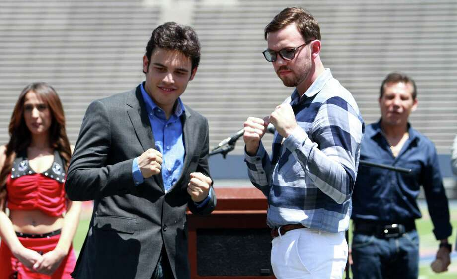 "In this photo taken April 24, 2012, Julio Cesar Chavez Jr. left, and his opponent Andy Lee pose for pictures during a news conference in the Sun Bowl stadium in El Paso, Texas. Chavez's father, former professional boxer Julio Cesar Chavez is watching at right background. Angry El Paso leaders on Wednesday accused the University of Texas system chancellor of fostering a ""climate of fear"" by canceling a high-profile boxing event in a border city fighting to overcome assumptions it has been overrun by spillover violence from the drug war in Mexico. City leaders were stunned when UT system Chancellor Francisco Cigarroa said Tuesday the University of Texas-El Paso's Sun Bowl stadium could not host a June 16 fight between WBC world middleweight champion Chavez, Jr., of Mexico and Andy Lee, of Ireland. The UT system said Cigarroa made the decision based on a ""higher than normal"" risk assessment but released no details. Photo: AP"