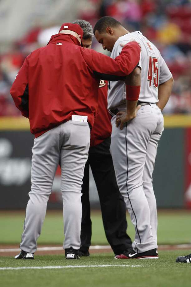 Carlos Lee is examined by Manager Brad Mills of the Houston Astros after injuring his leg during the game against the Cincinnati Reds at Great American Ball Park on April 27, 2012 in Cincinnati, Ohio. Photo: John Grieshop, Getty Images / 2012 Getty Images