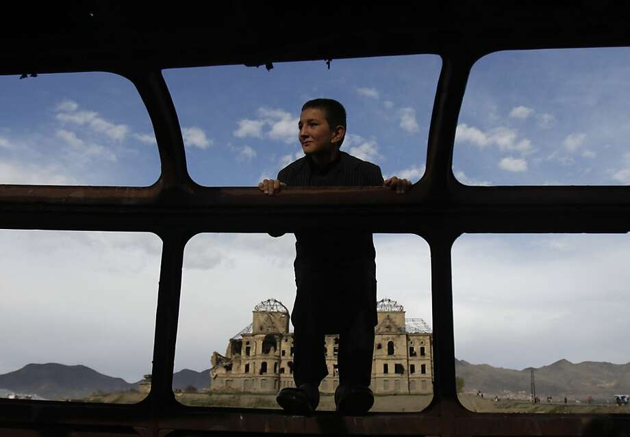 An Afghan boy plays in destroyed bus in front of the palace of former Afghan King Darul Aman, which was destroyed during the civil war, in Kabul, Afghanistan, Friday, April 27, 2012. (AP Photo/Ahmad Jamshid) Photo: Ahmad Jamshid, Associated Press