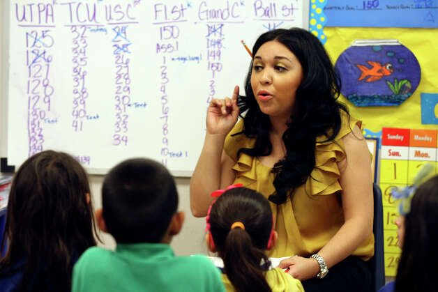 Teacher aide Gabrielle Ocomares helps out in a kinder English class at Weslaco IDEA Public Schools, Wednesday, April 11, 2012. Photo: JERRY LARA, San Antonio Express-News / SAN ANTONIO EXPRESS-NEWS