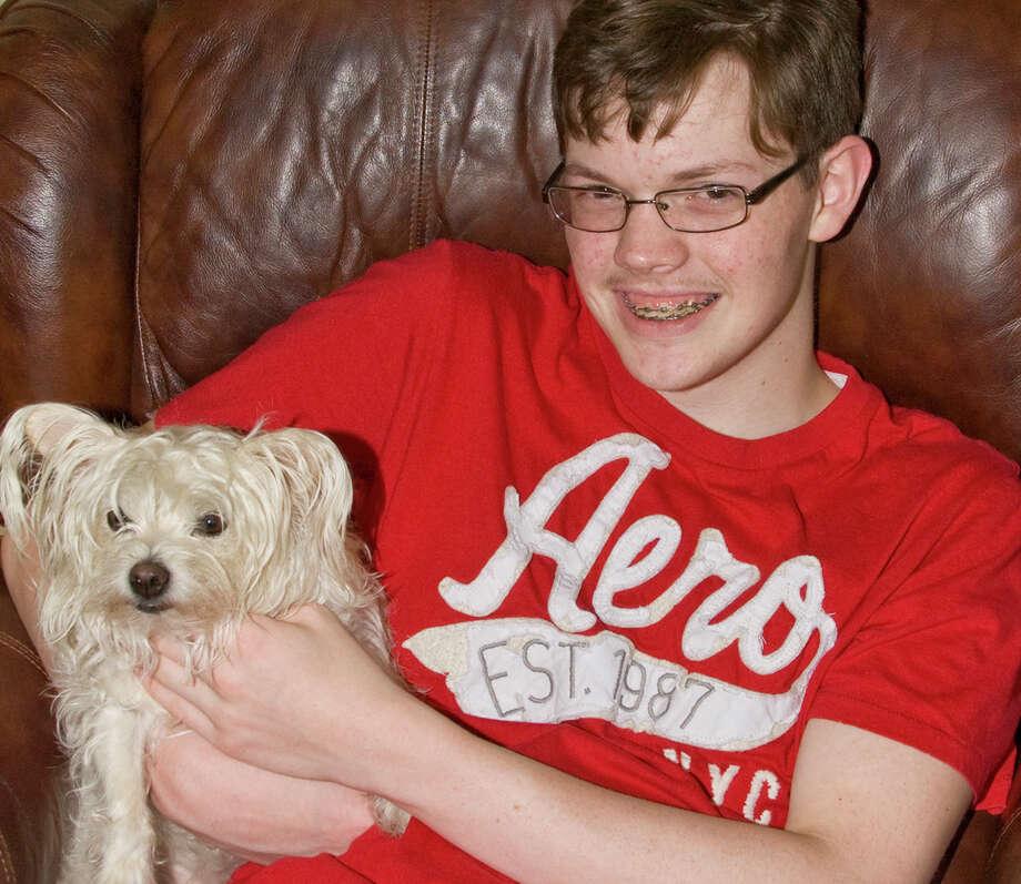 Jonathan Oliphint holds his dog at his home on Thursday in Bridge City, Texas. Photo: Matt Billiot / Houston Chronicle