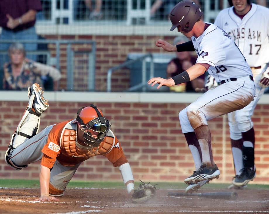 Texas A&M's Tyler Naquin (right) scores ahead of a tag attempt by Texas catcher Jacob Felts in the first inning Friday in College Station. The Aggies took the first game of the weekend series, with the next two slated for Austin. Photo: Stuart Villanueva, Bryan-College Station Eagle