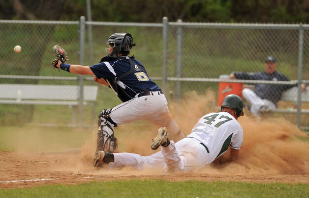 In a squeeze play, New Milford's Austin Kisling slides safe into home beating the throw to Notre Dame Fairfield's Anthony Searles giving New Milford the lead for the first time during their game at New Milford High School on Wednesday, April 18, 2012. New Milford won 10-6. Photo: Jason Rearick / The News-Times