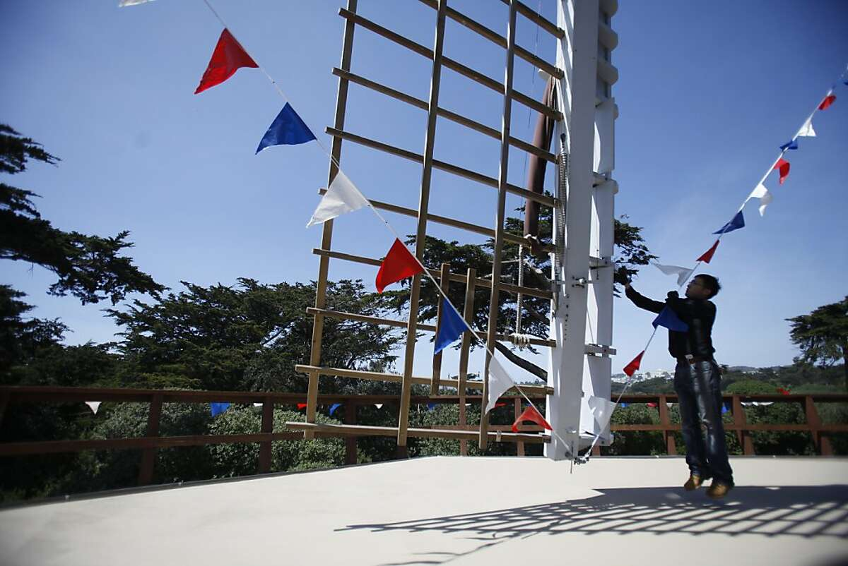 Kasing Shum San Francisco Recreation and Parks stationary engineer works next to the sails of the Dutch Windmill while making preparations for the Queen's Day festival on Friday, April 27, 2012 in San Francisco, Calif.