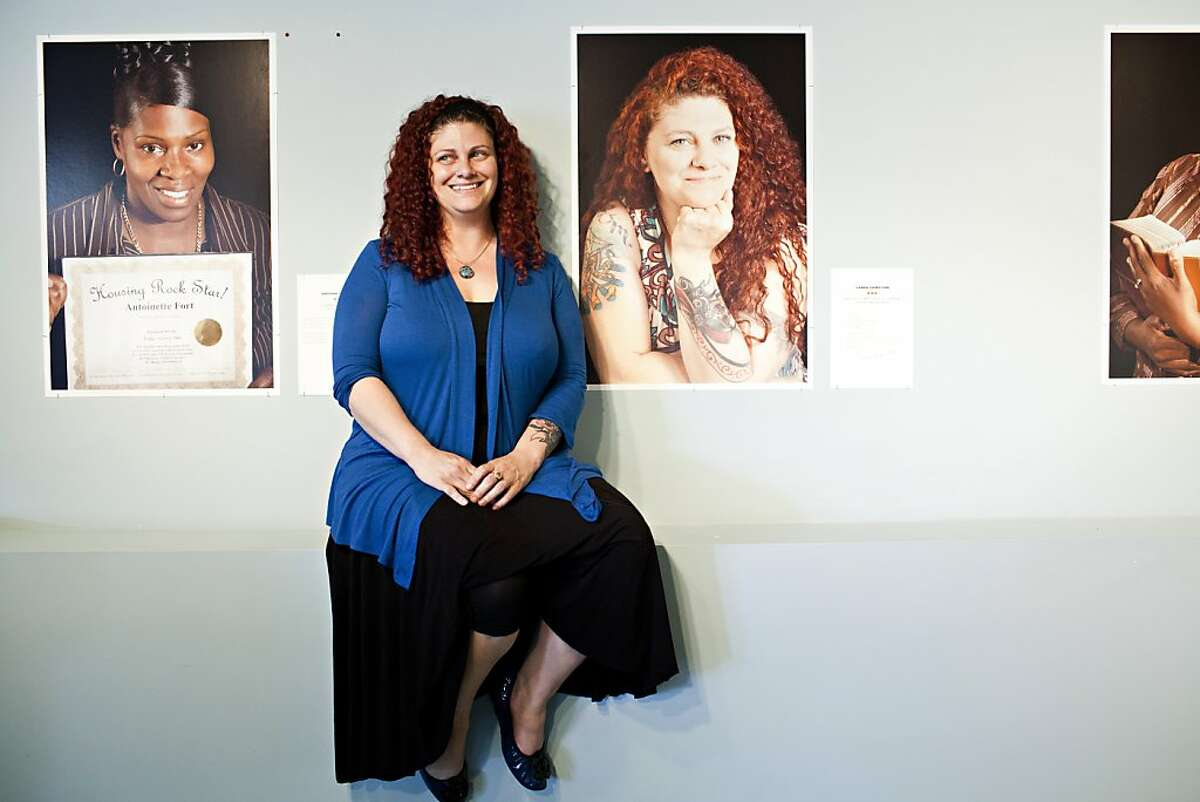 Carrie Hamilton, who works at the HPP, poses in front of a photograph of herself taken by Marsha Guggenheim from the exhibit,