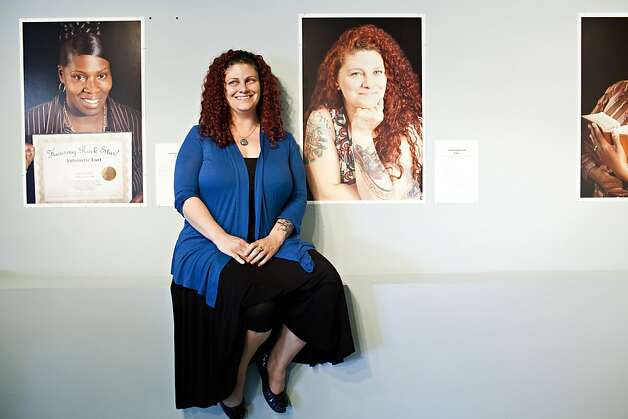 "Carrie Hamilton, who works at the HPP, poses in front of a photograph of herself taken by Marsha Guggenheim from the exhibit, ""Facing Forward,"" at the Homeless Prenatal Program in San Francisco, Calif., Thursday, April 26, 2012. The exhibit depicts 28 women who came from homelessness and despair, and in a yearlong course at the program learned how to become social workers.   Jason Henry/Special to The Chronicle Photo: Jason Henry, Special To The Chronicle"