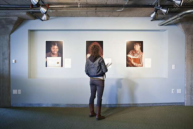 "A woman looks at a photograph by Marsha Guggenheim from her exhibit, ""Facing Forward,"" at the Homeless Prenatal Program in San Francisco, Calif., Thursday, April 26, 2012. The exhibit depicts 28 women who came from homelessness and despair, and in a yearlong course at the program learned how to become social workers.   Jason Henry/Special to The Chronicle Photo: Jason Henry, Special To The Chronicle"