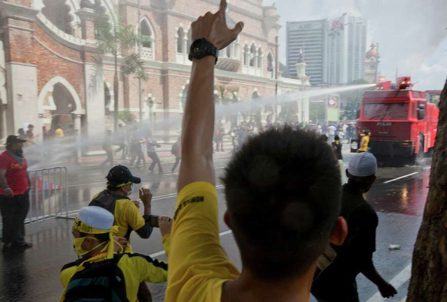 Protesters charge at a police vehicle as it sprays them with its water cannons in Kuala Lumpur, Mala