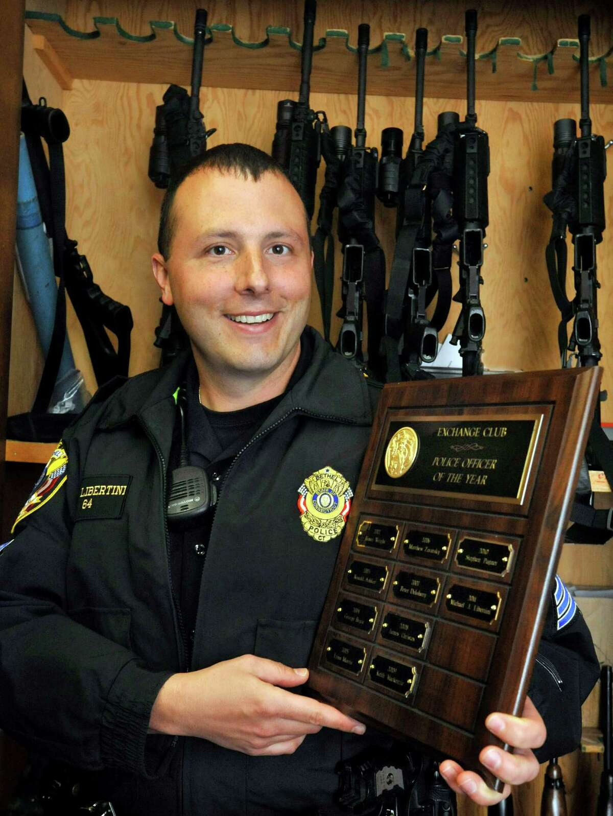 Sgt. Michael Libertini holds the Danbury Exchange Club plaque with his name as Bethel Police Officer of the Year at the Bethel Police Station Saturday, April 28, 2012.