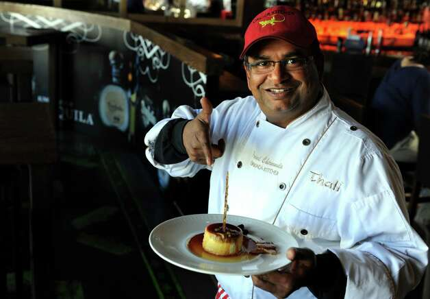 Chef Prasad Chirnomula holds the Mexicano at Oaxaca Kitchen in Westport, a Pepita scented caramel custard with chile specked coconut, crystal sugar and cocoa beans. Photo: Autumn Driscoll / Connecticut Post