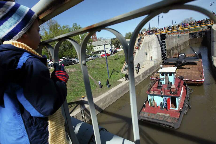 Rocco Mazzola, 6, of Waterford, watches as a barge carrying a vintage Douglas F-3D Skynight war plane from the Intrepid Sea, Air and Space Museum, passes through the Erie Canal lock 2, Saturday, April 28, 2012 in Waterford, N.Y. They are on their way to the Empire State Aerosciences Museum in Glenville, N.Y. Photo: Patrick Dodson, Associated Press / The Daily Gazette