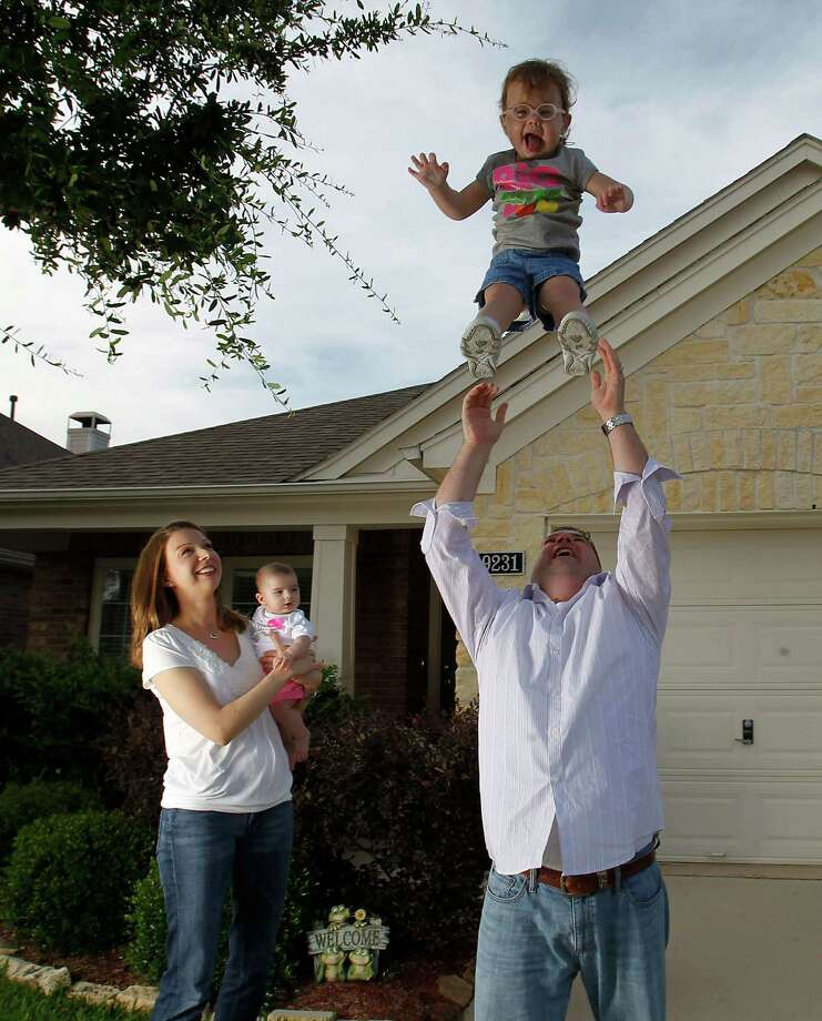 Thomas Stansel tosses Rachel, 2, into the air, while Amanda holds 4-month-old, Kayla, outside in their yard, Thursday, April 26, 2012, in Houston. Photo: Karen Warren, Houston Chronicle / 2012  Houston Chronicle