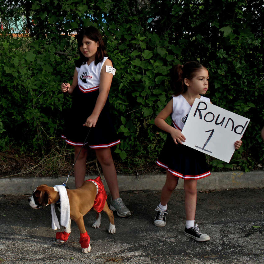 Bella Escamilla, 9, left, and her sister, Lily Escamilla, 6, stand with their dog, Blue, a boxer, during Canine Costume Contest before the Fiesta Pooch Parade in Alamo Heights on Saturday, April 28, 2012.
