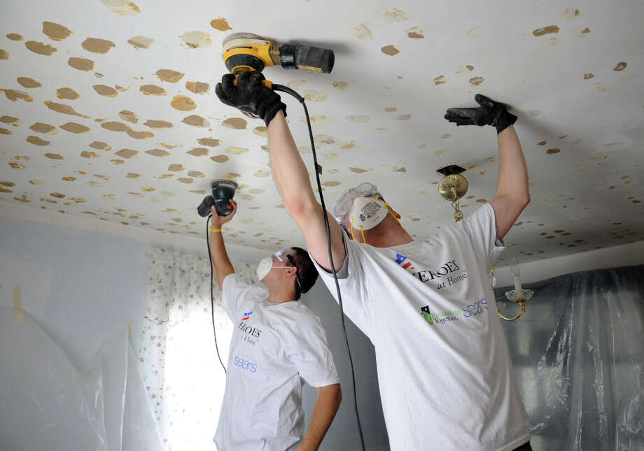 Dan, right, and Dominic, left, sand glue marks off the ceiling of Tyrone and Rudeon Spears' home during the Fairfeld County chapter of National Rebuilding Day on Saturday, April 28, 2012. The volunteers are part of a group of potential Navy Seals and asked that their last name not be used. Photo: Lindsay Niegelberg / Stamford Advocate