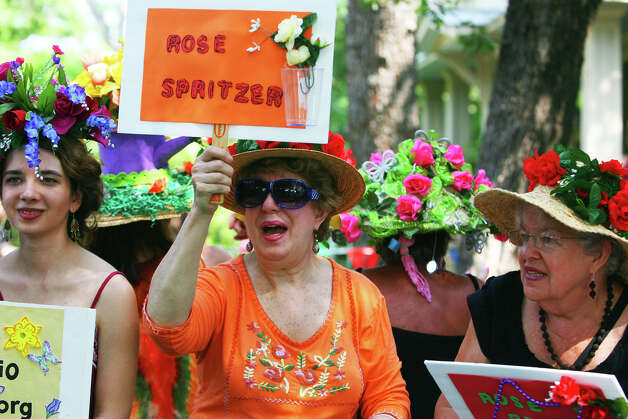 Women on the San Antonio Herb Society float hold signs as they ride down King William Street during the Fiesta King William Fair Parade, Saturday, April 28, 2012. (JENNIFER WHITNEY) Photo: JENNIFER WHITNEY, Jennifer Whitney/ Special To The Express-News / special to the Express-News