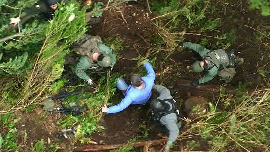 In this still frame taken from video provided by the King Co. Sheriff's Dept., a detective, center, is helped to the ground by other law-enforcement officers after he was lowered from a helicopter to an area near a deep-woods bunker, Saturday, April 28, 2012, in North Bend, Wash. Police, who had surrounded the bunker since Friday, found a dead body inside on Saturday.  Authorities earlier said they believed that Peter A. Keller, who is suspected of killing his wife and daughter last week, was hiding out in the bunker. Photo: Associated Press