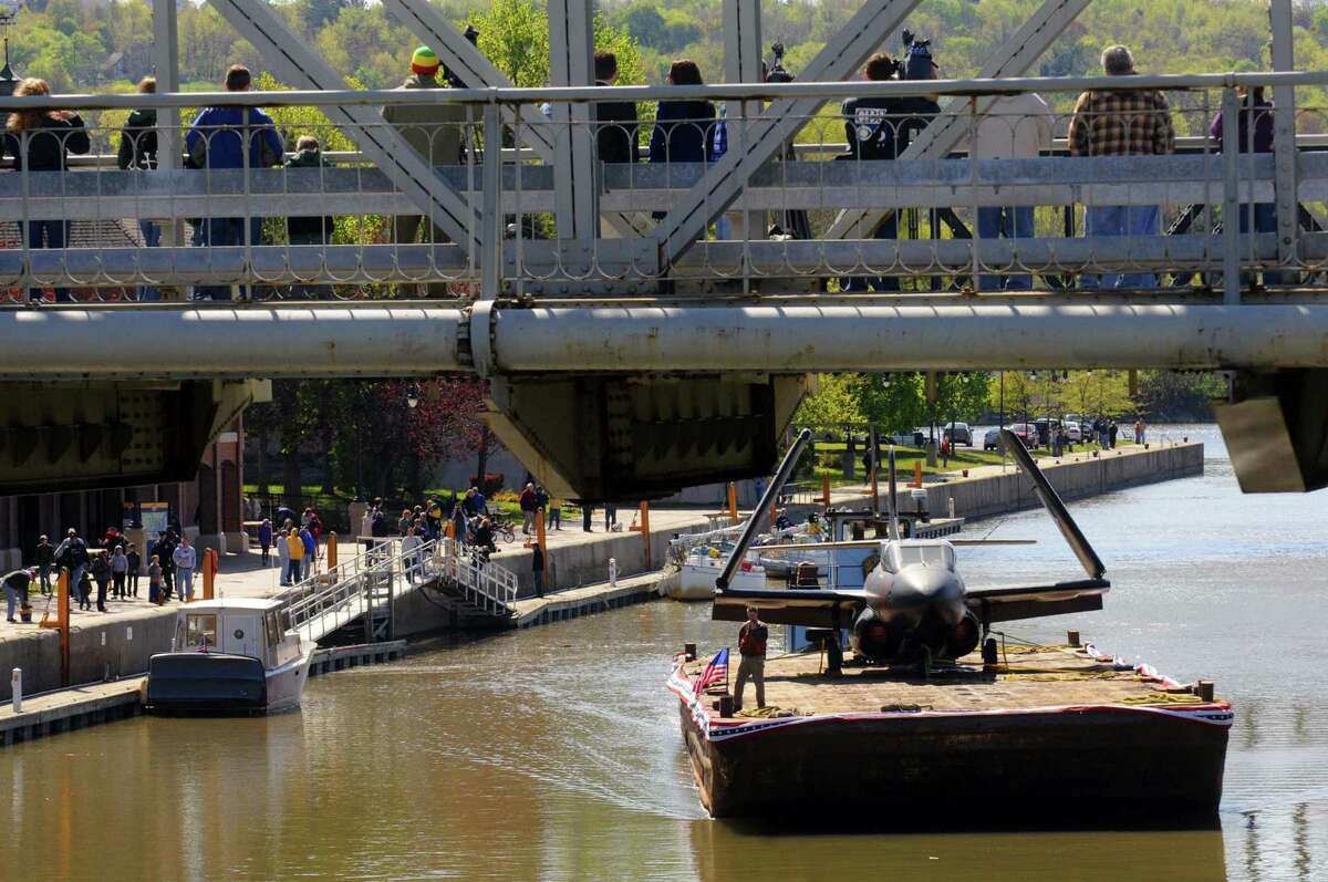 Crowds gather to watch a barge carrying one of the three planes from the USS Intrepid museum make it's way toward Lock 2 of the Erie Canal in Waterford N.Y. Saturday April 28, 2012. (Michael P. Farrell/Times Union)