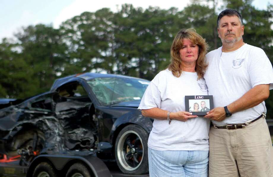 Kae Pennywell, left, and husband, Dennis, right, hold a photo of their son, Aaron, and his girlfriend at the time, as they stand in front of his wrecked car on display Saturday in northwest Harris County. Aaron was killed last year when the car he was driving was struck by an intoxicated driver. Photo: Cody Duty / © 2011 Houston Chronicle