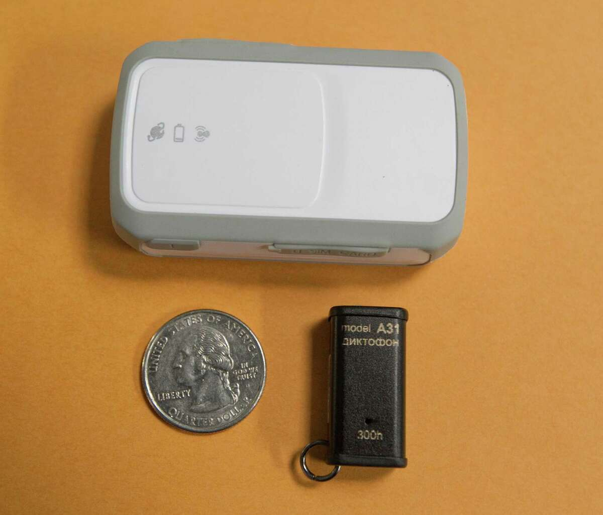 A Russian mini audio recorder, bottom, and a mini GPS tracking device and magnetic case are some of the most popular items being used in surveillance.