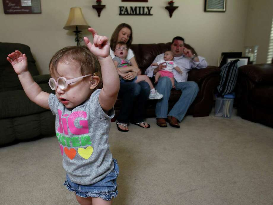 Haley Stansel, 2, walks through the room as Amanda Stansel holds Rachel, 2, and husband Thomas holds 4-month-old Kayla, in their home, Thursday, April 26, 2012, in Houston. Thomas and Amanda Stansel became parents of sextuplets born just shy of 23 weeks in June 2009. Haley and Rachel were the only sextuplets to survive.  Photo: Karen Warren, Houston Chronicle / © 2012  Houston Chronicle