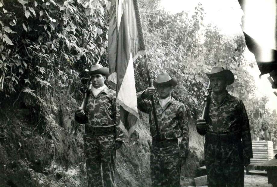 Three members of Brigade 2506's honor guard stand with their new unit flag while training at Trax Base before the Bay of Pigs invasion.