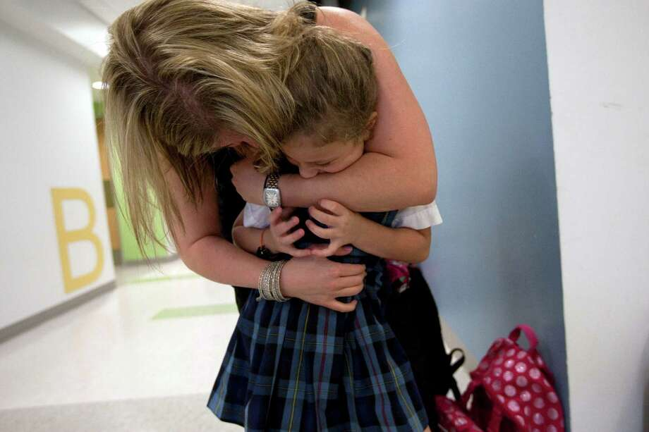Willa Berry, 6, gets a hug from family friend and her brother Aaron's teacher Lindsay Tavor as Willa walked through the hall of the Beth Yeshurun Day School where he attends school with his brothers and cousins, Thursday, April 5, 2012, in Houston. Photo: Johnny Hanson, Houston Chronicle / © 2012  Houston Chronicle