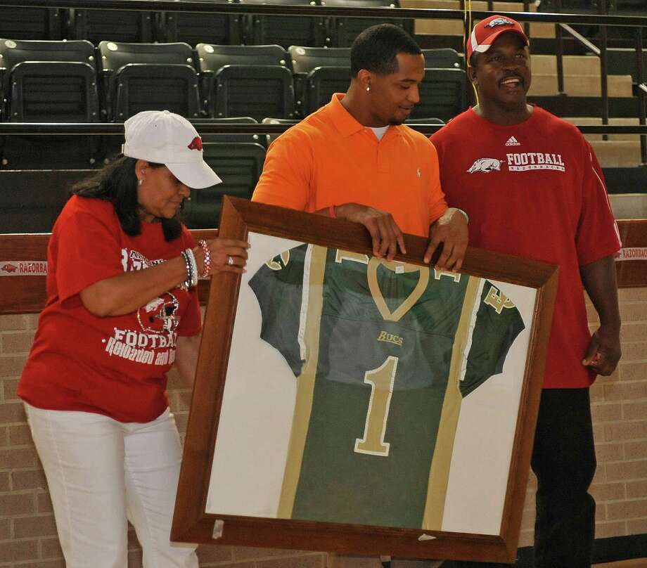 During the watch, a ceremony was held retiring his high school jeresy. Tramain Thomas, center, an East Chambers High School graduate and a former University of Arkansas football player, stands with his mother Carla, left, and his dad, Billy Thomas Sr. right, hoists the framed jersey to the crowd.  He was there waiting to be selected in the NFL Draft Saturday April 28, 2012. During the televised draft, the high school hosted a draft watching party for Thomas.   Dave Ryan/The Enterprise