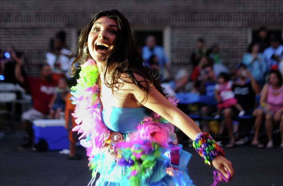 Entertainer Ara Celi enjoys herself as she participates in the Fiesta Flambeau Parade on Saturday, April 28, 2012. The parade website says that this is the largest illuminated parade in America. Photo: BILLY CALZADA, SAN ANTONIO EXPRESS-NEWS / San Antonio Express-News