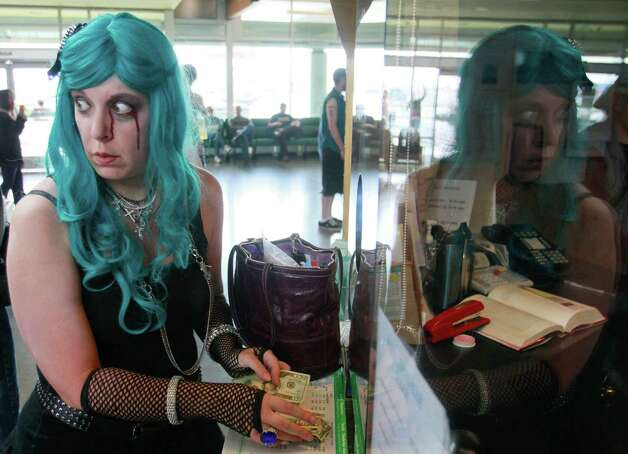 Dressed as a zombie, Jennifer Costales purchases a ferry ticket at the Seattle ferry terminal. Photo: SOFIA JARAMILLO / SEATTLEPI.COM