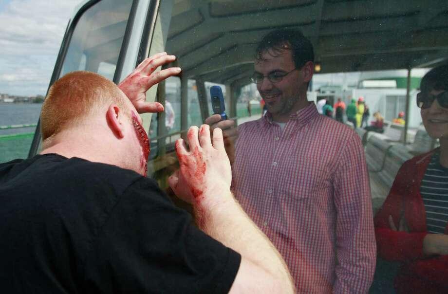 A ferry rider snaps photos of a zombie. Photo: SOFIA JARAMILLO / SEATTLEPI.COM