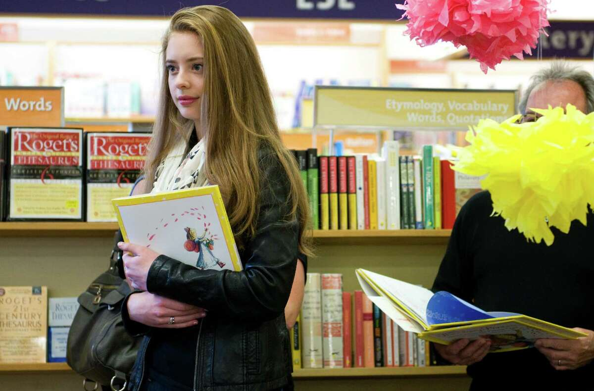 Ashlyn Pearce, 17, daughter of the bookstore's CEO, waits to be the first to have her book signed by Julie Andrews.