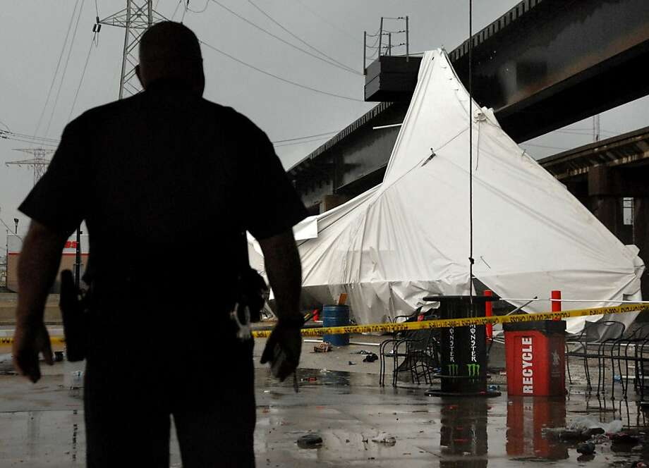 An officer from the Terminal Railroad Police Department surveys a party tent from Kilroy's Sports Bar in St. Louis as it rests against a railroad trestle near the bar after storm winds blew through the area following a baseball game between the St. Louis Cardinals and Milwaukee Brewers at nearby Busch Stadium Saturday, April 28, 2012. One person died Saturday and more than a dozen were taken to a hospital with injuries after high winds blew over a beer tent near Busch Stadium in St. Louis. (AP Photo/Sid Hastings) Photo: Sid Hastings, Associated Press