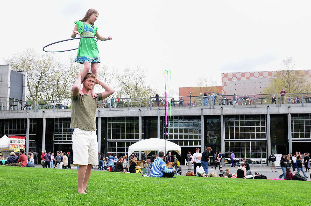 Eukia Lemaster, 10, hula hoops on the shoulders of her father, Sun Lemaster, outside the Seattle Center Pavilion at the 19th annual World Rhythm Festival.