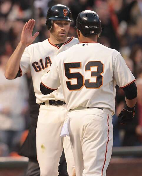Giants Nate Schierholtz and Melky Cabrera celebrate scoring two runs in the seventh inning at AT&T P
