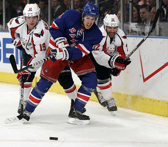 New York Rangers' Michael Del Zotto (4) clears the puck as Washington Capitals' Nicklas Backstrom (19) and Mike Knuble (22) chase during the first period of Game 1 in the second round of the NHL hockey Stanley Cup playoffs Saturday, April 28, 2012, in New York. Photo: Frank Franklin II, Associated Press