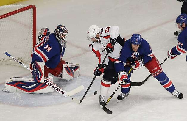 Washington Capitals' Troy Brouwer (20) is defended by New York Rangers' Dan Girardi (5) and goalie Henrik Lundqvist (30) during the second period of Game 1 in the second round of the NHL hockey Stanley Cup playoffs Saturday, April 28, 2012, in New York. Photo: Frank Franklin II, Associated Press