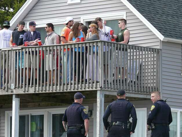 Police keep an eye on students partying at the annual Clam Jam at Lantern Point on Saturday. Photo: Genevieve Reilly / Fairfield Citizen