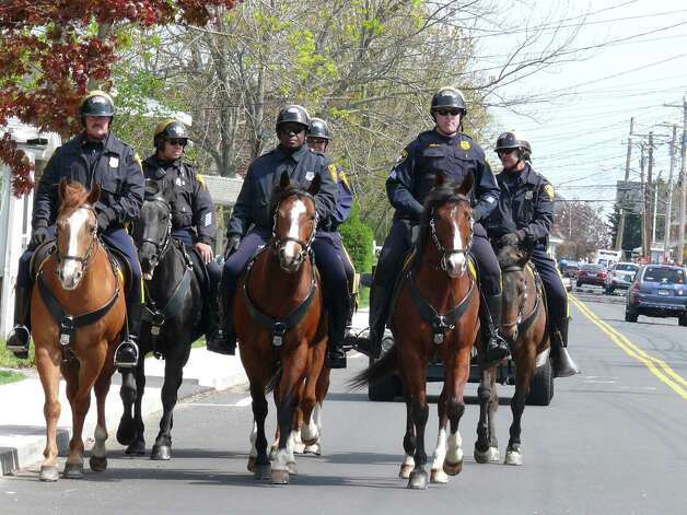 A deployment of horse-mounted police officers from the Bridgeport Police Department helped to control crowds in the Fairfield Beach neighborhood during Saturday's Clam Jam party. Photo: Genevieve Reilly / Fairfield Citizen