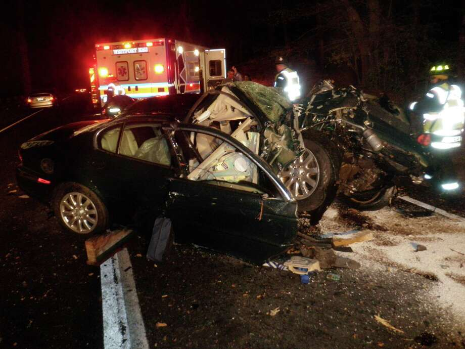 A Jaguar was heavily damaged and its driver hospitalized after smashing into a tree off the Merritt Parkway at the Westport/Fairfield border Saturday night. Photo: Westport Fire Department / Westport News contributed