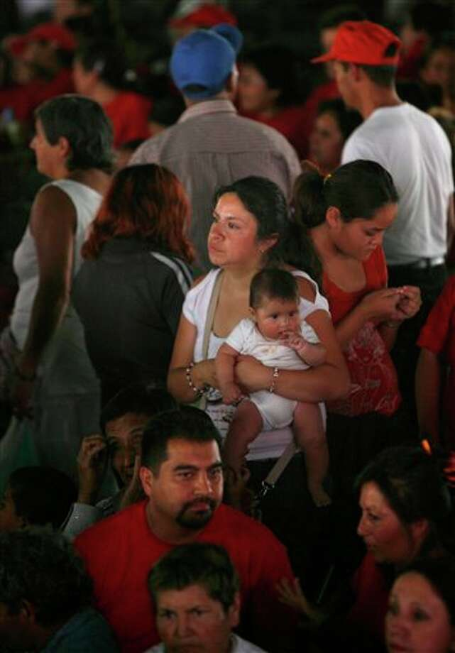 A woman holds a baby as she attends a campaign rally for presidential candidate Enrique Pena Nieto, of the Institutional Revolutionary Party (PRI), in Nezahualcoyotl, Mexico, Saturday, April 28, 2012. Mexico will hold presidential elections on July 1. (AP Photo/Marco Ugarte) Photo: Marco Ugarte, Associated Press / AP