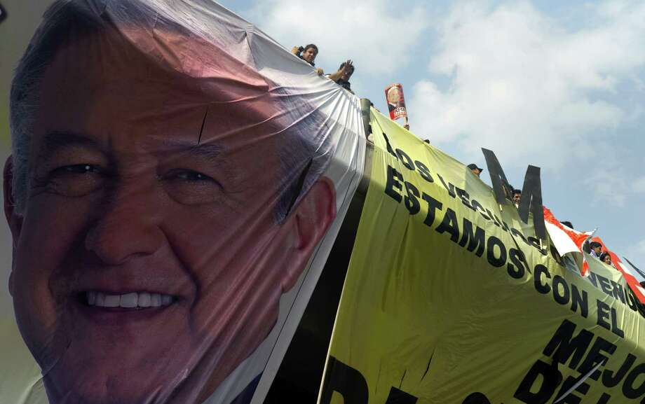 Supporters of Mexican presidential candidate for the leftist coalition Progressive Movement of Mexico, Andres Manuel Lopez Obrador, remain next to giant banners during a rally at the Venustiano Carranza square in Mexico City, on April 16, 2012. Mexico will hold presidential elections next July 1.  AFP PHOTO/ Yuri CORTEZ Photo: YURI CORTEZ, Getty Images / 2012 AFP