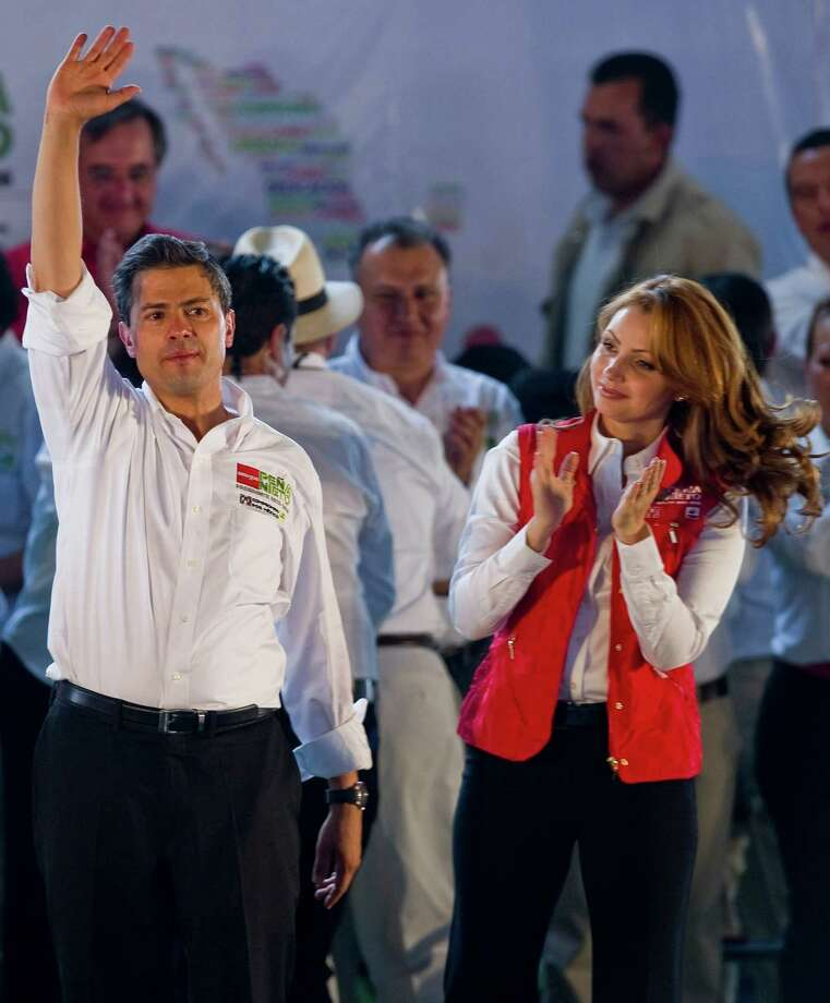 Mexican presidential candidate for the Institutional Revolutionary Party (PRI), Enrique Pena Nieto (L) and his wife Angelica Rivera (R), gesture during a rally in Nezahualcoyotl, Mexico State, Mexico on April 28, 2012. Mexico will hold presidential elections next July 1, 2012. AFP PHOTO/Alfredo ESTRELLA        (Photo credit should read ALFREDO ESTRELLA/AFP/GettyImages) Photo: ALFREDO ESTRELLA, Getty Images / 2012 AFP