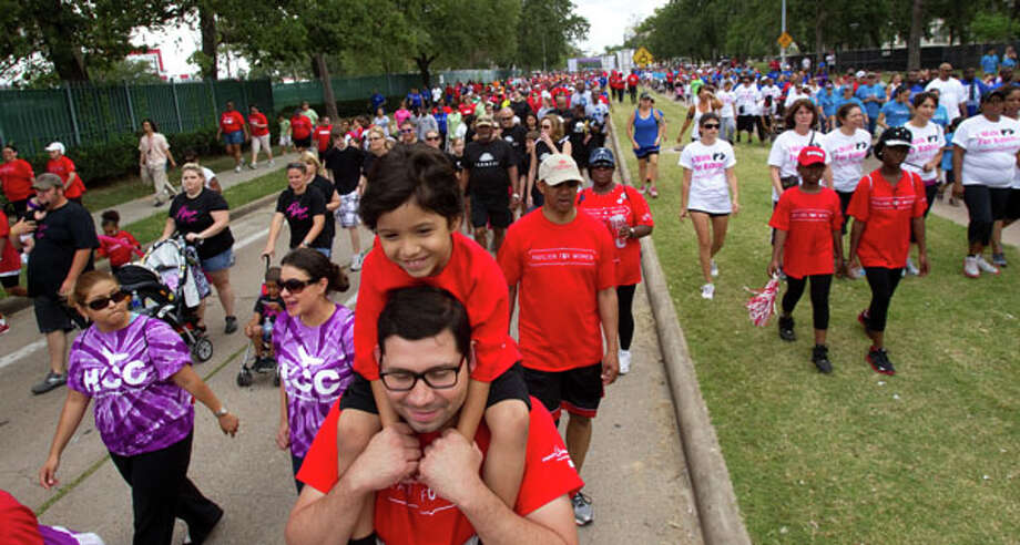 Paola Silva rides on the shoulders of his father, Eric Silva, during the Houston March for Babies Sunday, April 29, 2012, in Houston. Thousands of walkers took to the streets around the University of Houston campus to raise money for the March of Dimes, supporting lifesaving research and community programs that help mothers have healthy, full-term pregnancies and strong, healthy babies. ( Brett Coomer / Houston Chronicle ) Photo: Brett Coomer, Houston Chronicle / © 2012 Houston Chronicle