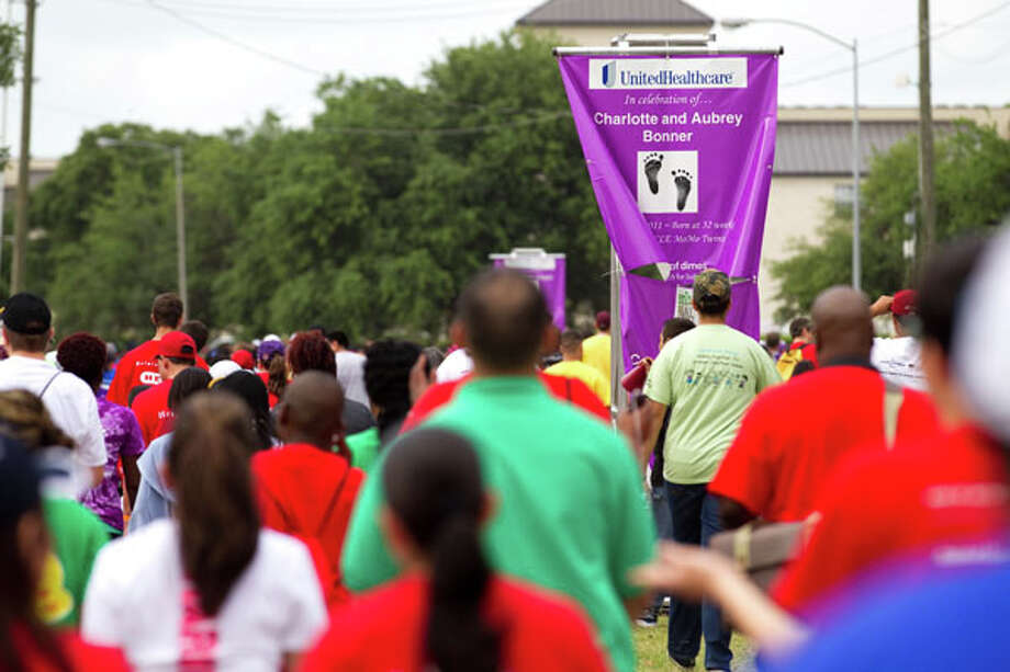 One of many signs celebrating healthy children line the route as walkers take to the streets during the Houston March for Babies Sunday, April 29, 2012, in Houston. Thousands of walkers took to the streets around the University of Houston campus to raise money for the March of Dimes, supporting lifesaving research and community programs that help mothers have healthy, full-term pregnancies and strong, healthy babies. ( Brett Coomer / Houston Chronicle ) Photo: Brett Coomer, Houston Chronicle / © 2012 Houston Chronicle