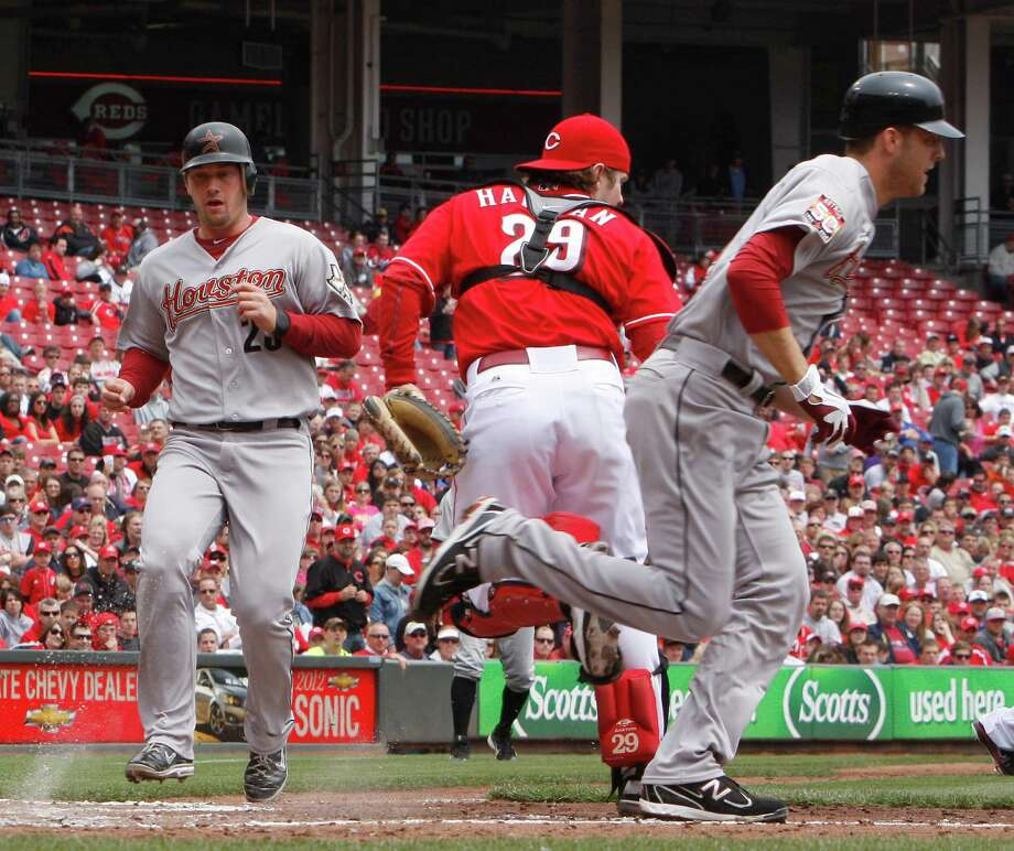 Houston Astros' Jordan Lyles, right, bunts as teammate Chris Johnson, left, scores during the second inning of a baseball game against the Cincinnati Reds, Sunday, April 29, 2012, in Cincinnati. Reds catcher Ryan Hanigan, center, awaits the throw. The Reds came from behind to win 6-5. (AP Photo/David Kohl) Photo: DAVID KOHL, Associated Press / FR51830 AP