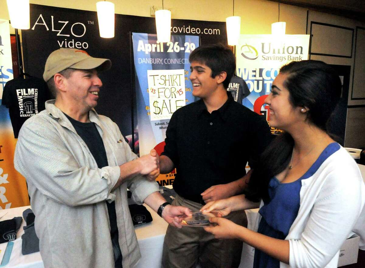 Tom Carruthers accepts a film by Bethel High School students Justin Fargiano, 14, and his sister, Olivia Fargiano, 16, at the Palace theater in Danbury for the screening of the