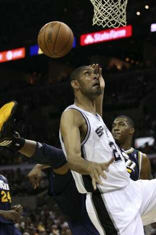 Spurs forward Tim Duncan goes for a rebound against Utah Jazz forward Derrick Favors during the first half of game one of the Western Conference first round at the AT&T Center, Sunday, April 29, 2012. Jerry Lara/San Antonio Express-News (Jerry Lara / San Antonio Express-News)