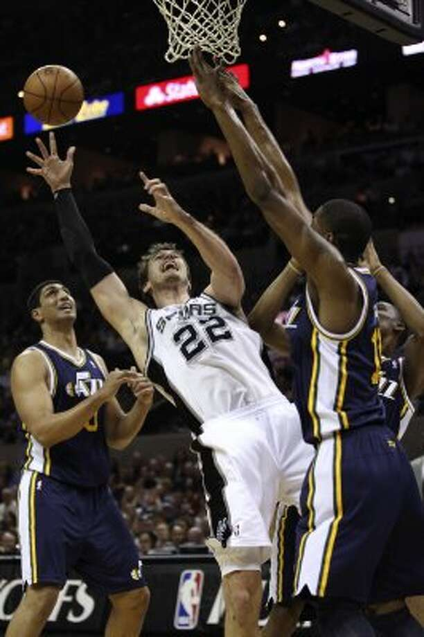 The Spurs' Tiago Splitter goes from a rebound between Utah Jazz Enes Kanter, left, and Derrick Favors during the first half of game one of the Western Conference first round at the AT&T Center, Sunday, April 29, 2012. Jerry Lara/San Antonio Express-News (Jerry Lara / San Antonio Express-News)