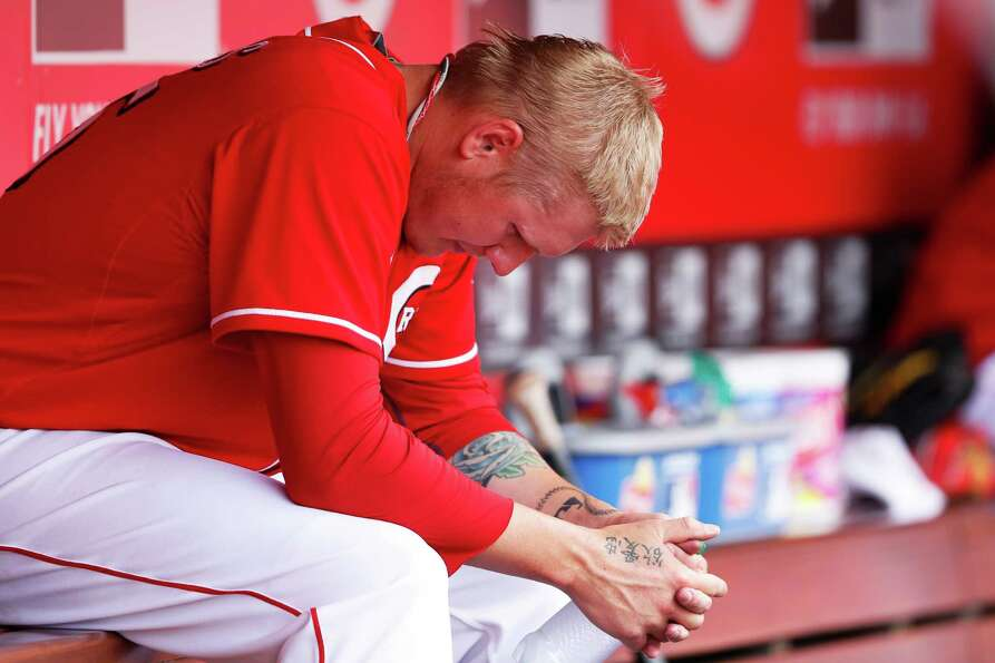 Mat Latos of the Cincinnati Reds reacts after being taken out of the game in the seventh inning agai